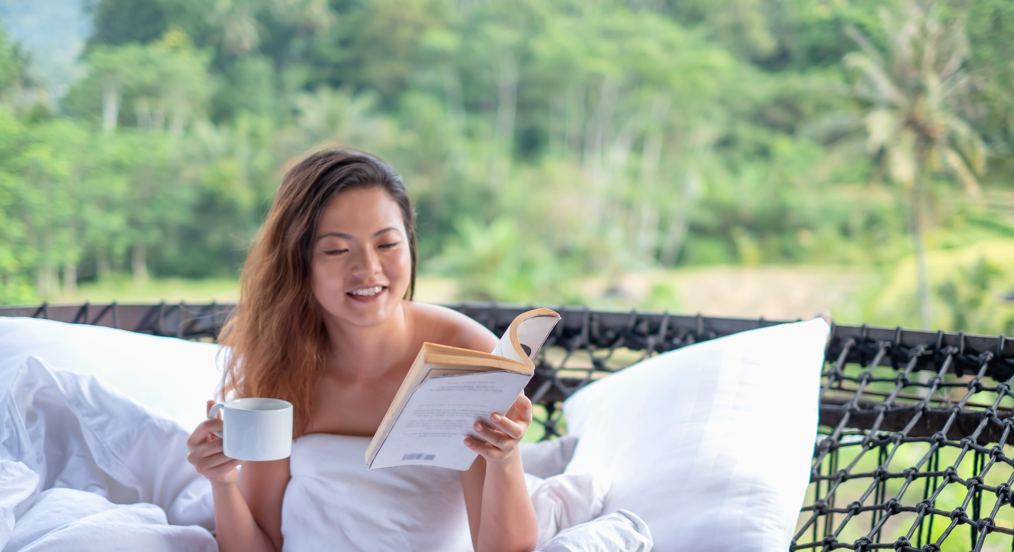 Shot of a beautiful Asian traveler reading book while drinking her morning coffee. She's sitting on an outdoor suspended net hammock bed. There is a white pillow beside her and a duvet that covering her body.