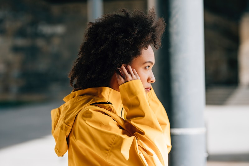 A portrait of a beautiful young woman in a yellow jacket, putting earphones on and preparing for a jog in the city