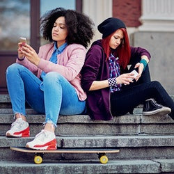 Two people sit back to back on stairs outside, facing away from each other while texting. Breaking up with friends post-pandemic can be tough, but it's alright to disengage when you need to.