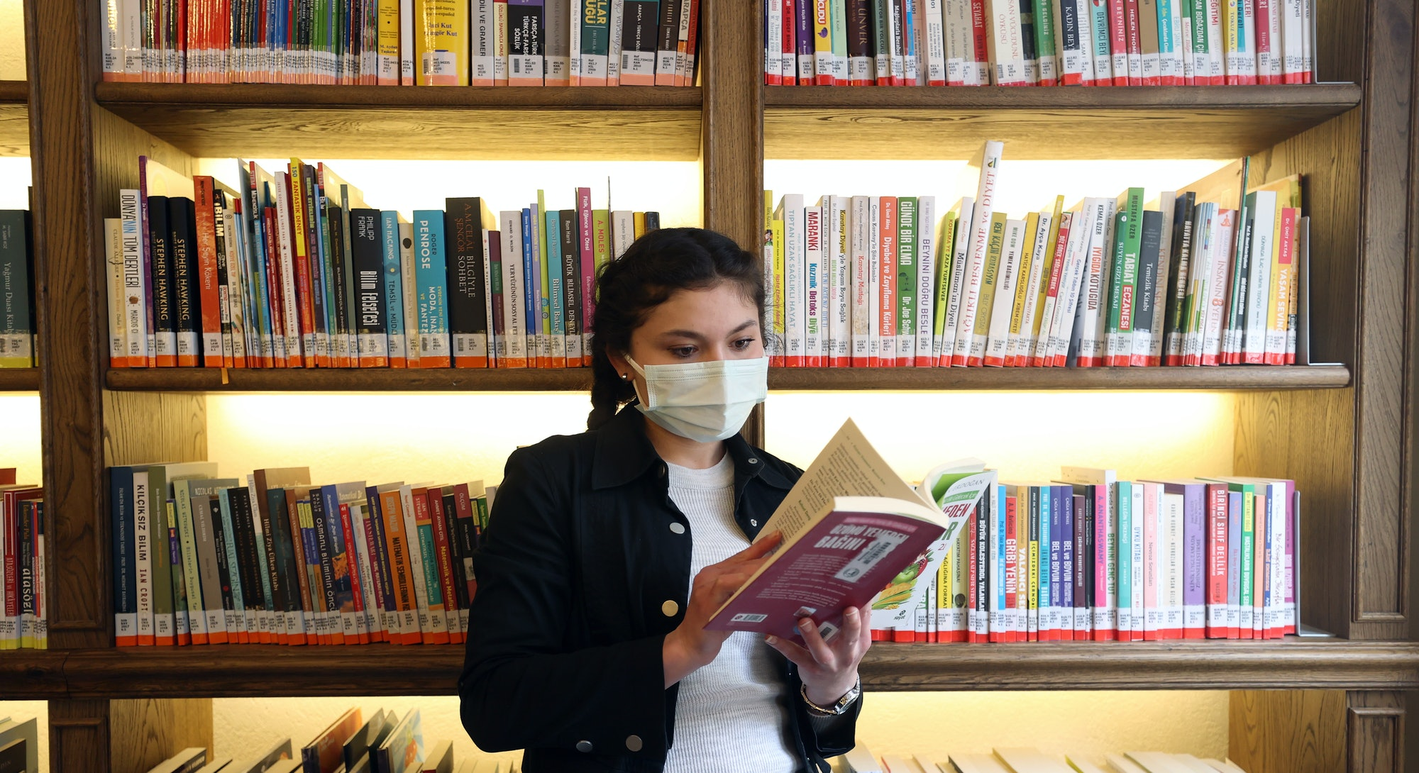 ISTANBUL, TURKEY - APRIL 01: A woman inspects books at Nevmekan Selimiye Library serving within the ...