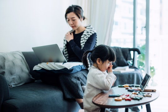 Exhausted young Asian mother and little daughter rubbing tired eyes while working from home on lapto...