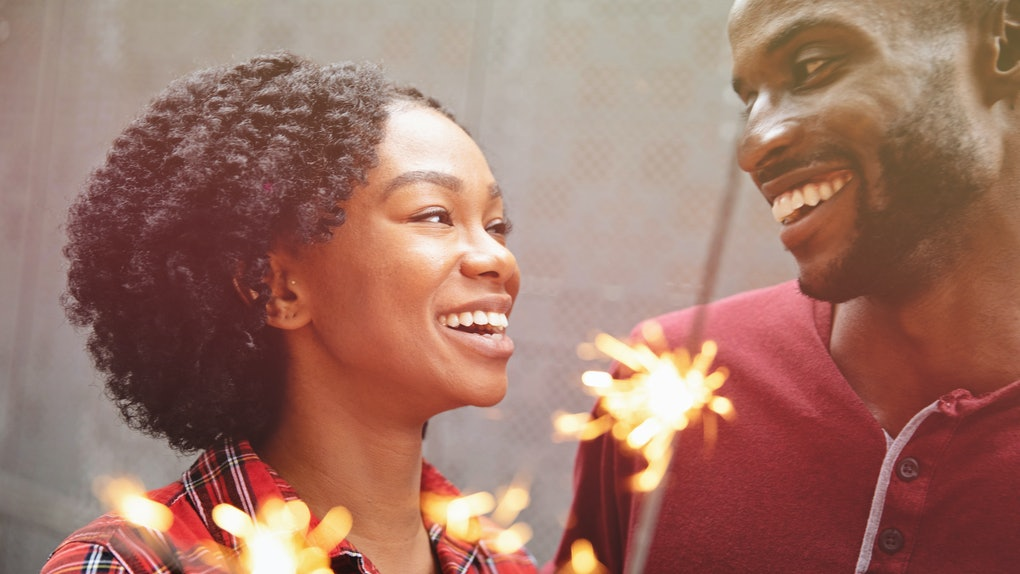 Couple celebrating with sparklers and sharing warm smiles