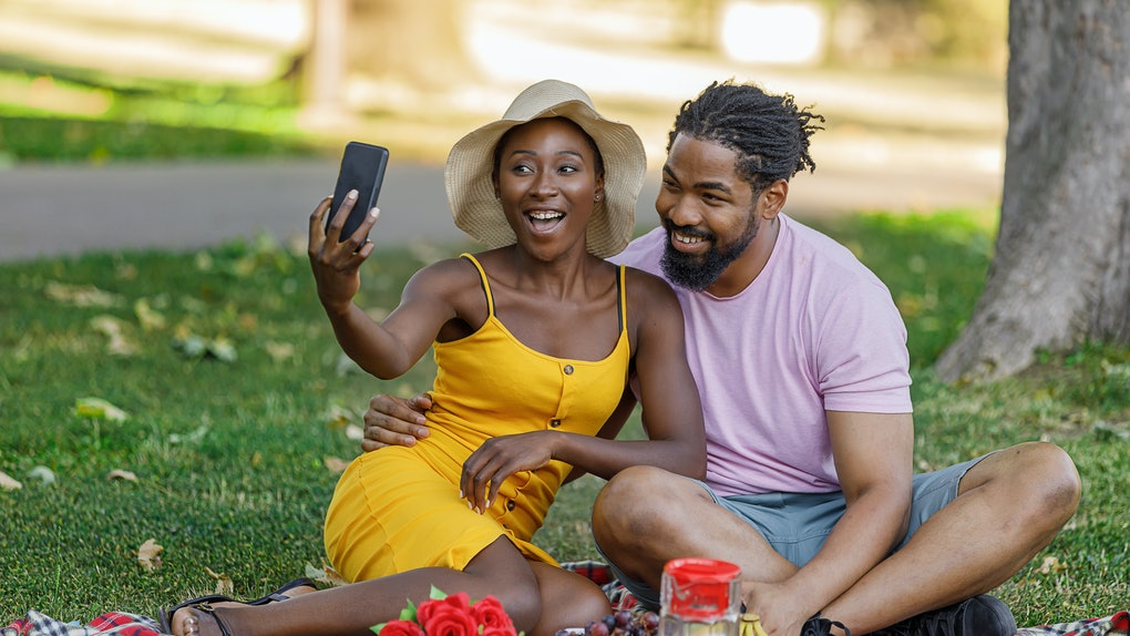 A Happy Couple of African-American Ethnicity is on a Picnic in a Nature. They are Enjoying in Delicious Tropical Fruit and Having a Lot of Fun While Taking a Selfie Photos.