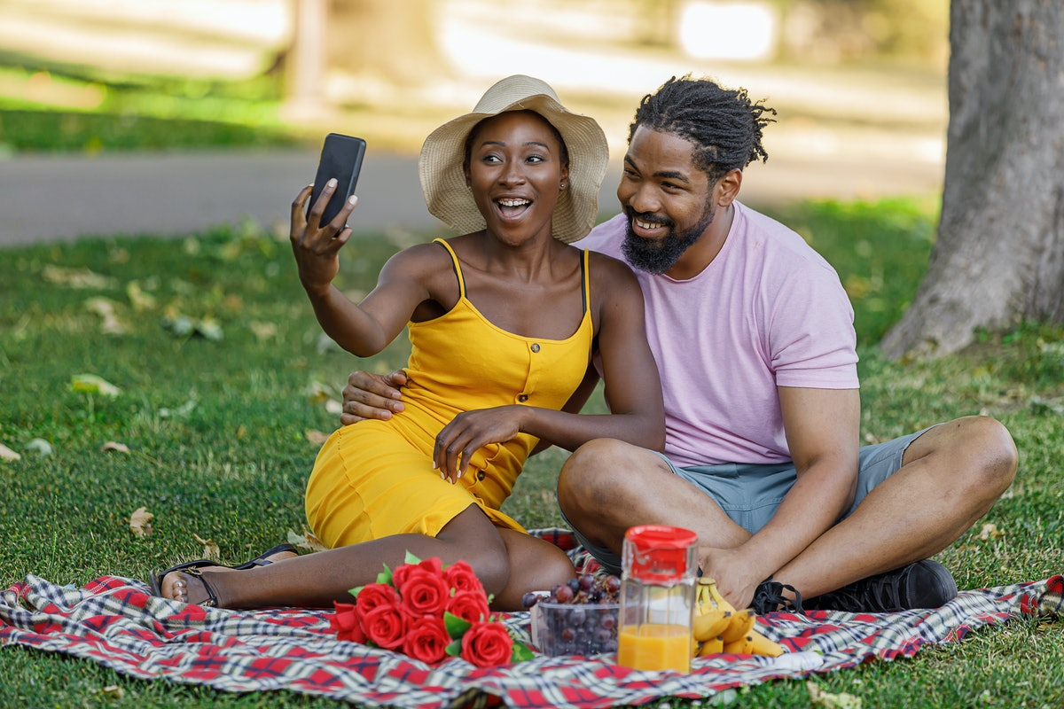 A Happy Couple of African-American Ethnicity is on a Picnic in a Nature. They are Enjoying in Delici...