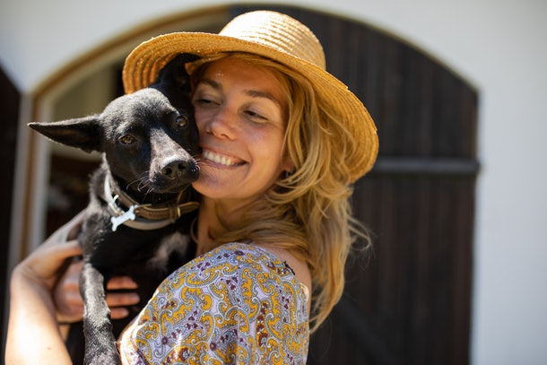 A pretty young woman with a hat is holding a cute black mixed breed in her arms and smiling