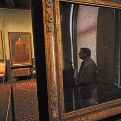 """BOSTON, MA - FEBRUARY 19: Anthony Amore, security director of the Isabella Stewart Gardner Museum, is reflected in the empty frame which held the painting """"The Concert"""" by Vermeer in the Dutch Room of the museum in Boston on Feb. 19, 2019. Amore's office on the fourth floor of the historic museum is adorned with images of some of the worlds most coveted masterpieces by Rembrandt and Vermeer, reminders of the $500 million worth of artwork stolen 29 years ago. (Photo by Suzanne Kreiter/The Boston Globe via Getty Images)"""