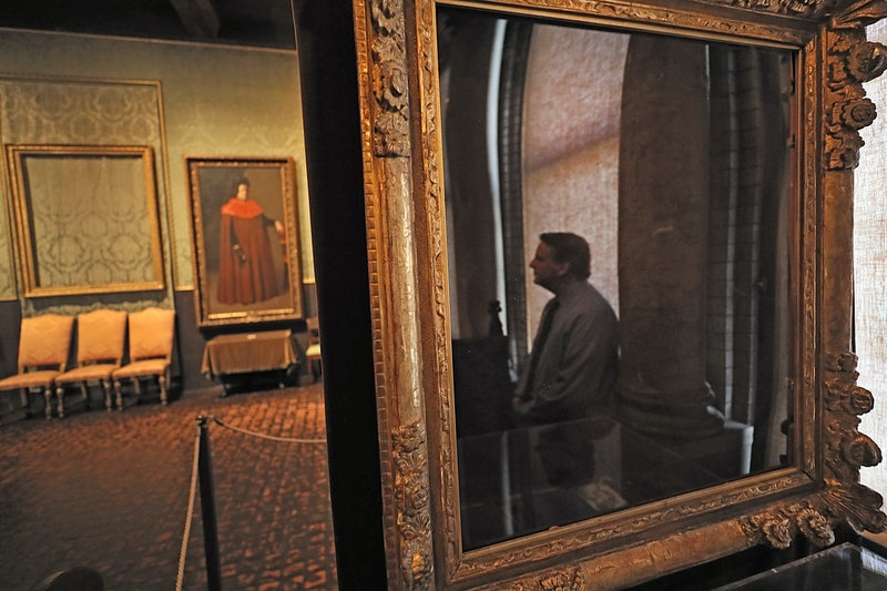 "BOSTON, MA - FEBRUARY 19: Anthony Amore, security director of the Isabella Stewart Gardner Museum, is reflected in the empty frame which held the painting ""The Concert"" by Vermeer in the Dutch Room of the museum in Boston on Feb. 19, 2019. Amore's office on the fourth floor of the historic museum is adorned with images of some of the worlds most coveted masterpieces by Rembrandt and Vermeer, reminders of the $500 million worth of artwork stolen 29 years ago. (Photo by Suzanne Kreiter/The Boston Globe via Getty Images)"