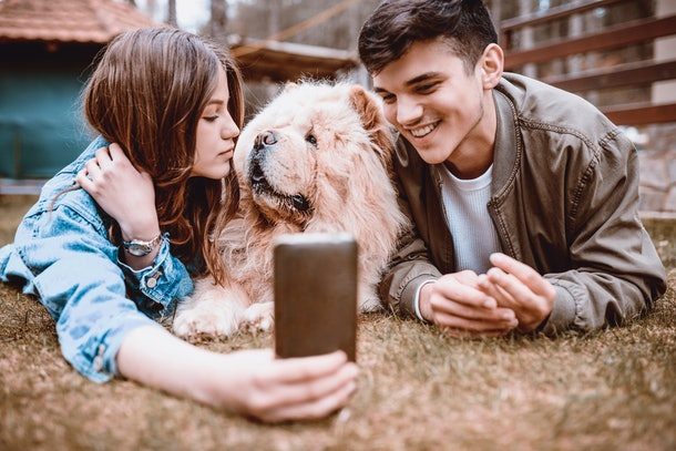A happy couple takes a selfie in the backyard with their dog.