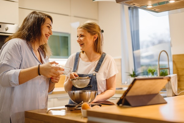 Two happy friends bake a dessert in the kitchen.