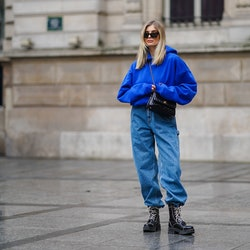 PARIS, FRANCE - MARCH 11: Xenia Adonts wears sunglasses from Linda Farrow, a bold blue hoodie sweater from Cherry LA, a black leather quilted Chanel bag, blue denim baggy jeans with side cargo pockets from Miu Miu, black leather boots from Alexa Chung, on March 11, 2021 in Paris, France. (Photo by Edward Berthelot/Getty Images)