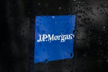 JP Morgan logo displayed on a phone screen is seen through raindrops on the window in this illustrat...