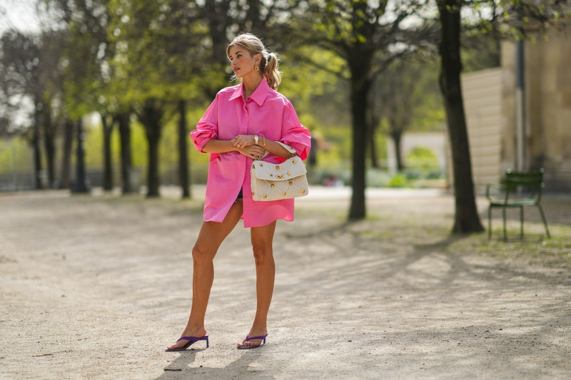 PARIS, FRANCE - APRIL 01: Xenia Adonts wears golden earrings, a neon pink long oversized shirt / dress from Valentino, a white Valentino studded bag, a golden watch, a golden bracelet, purple Valentino shoes / sandals, during a street style fashion photo session, on April 01, 2021 in Paris, France. (Photo by Edward Berthelot/Getty Images)