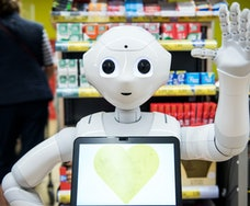 """08 April 2020, Schleswig-Holstein, Ahrensburg: A robot called """"Pepper"""" is standing in front of the cash registers in a supermarket. Since the beginning of the week, the humanoid robot has been informing the store's customers about the rules of conduct in connection with the Corona pandemic. (to dpa """"Robot """"Pepper"""" admonishes in Ahrensburg supermarket to corona rules"""") Photo: Daniel Bockwoldt/dpa (Photo by Daniel Bockwoldt/picture alliance via Getty Images)"""