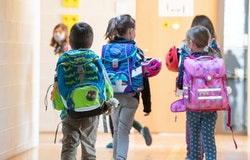 22 February 2021, Bavaria, Munich: Children walk down a hallway of their school with their satchels. Photo: Peter Kneffel/dpa (Photo by Peter Kneffel/picture alliance via Getty Images)