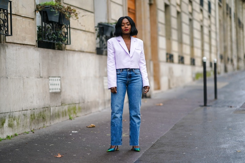 PARIS, FRANCE - DECEMBER 12: Carrole Sagba wears a pale purple / mauve blazer cropped jacket from Leandon Cano, black bras, blue jeans from Zara, blue and green shiny pointy glittering shoes from Amina Muaddi, on December 12, 2020 in Paris, France. (Photo by Edward Berthelot/Getty Images)
