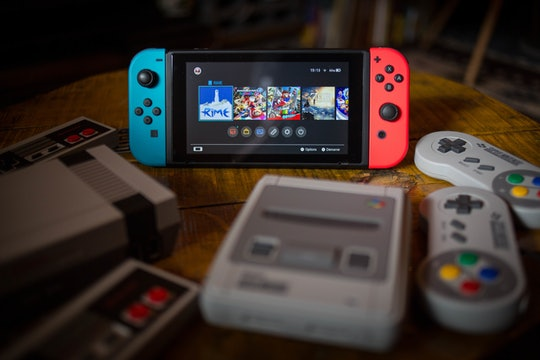 BANGKOK, THAILAND - 2019/01/08:  In this photo illustration, a Nintendo Switch (M) surrounded by a NES (Nintendo Entertainment System) Classic Mini (L) and a SNES (Super Nintendo Entertainment System) Classic Mini (R) video game consoles. (Photo Illustration by Guillaume Payen/SOPA Images/LightRocket via Getty Images)