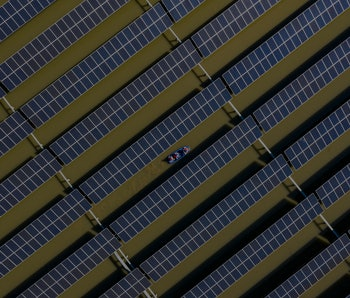 HAI AN, CHINA - APRIL 06: Workers carry out maintenance on solar panels installed atop a fish pond at a fishery-solar hybrid photovoltaic power station on April 6, 2021 in Hai an, Jiangsu Province of China. (Photo by Zhai Huiyong/VCG via Getty Images)