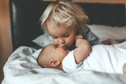 Little brother hugging his newborn sister. Toddler kid meeting new sibling. Cute boy and new born baby girl relax in a white bedroom. Family with children at home. Love, trust and tenderness