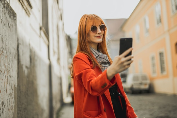 Young lady using a phone while on the street