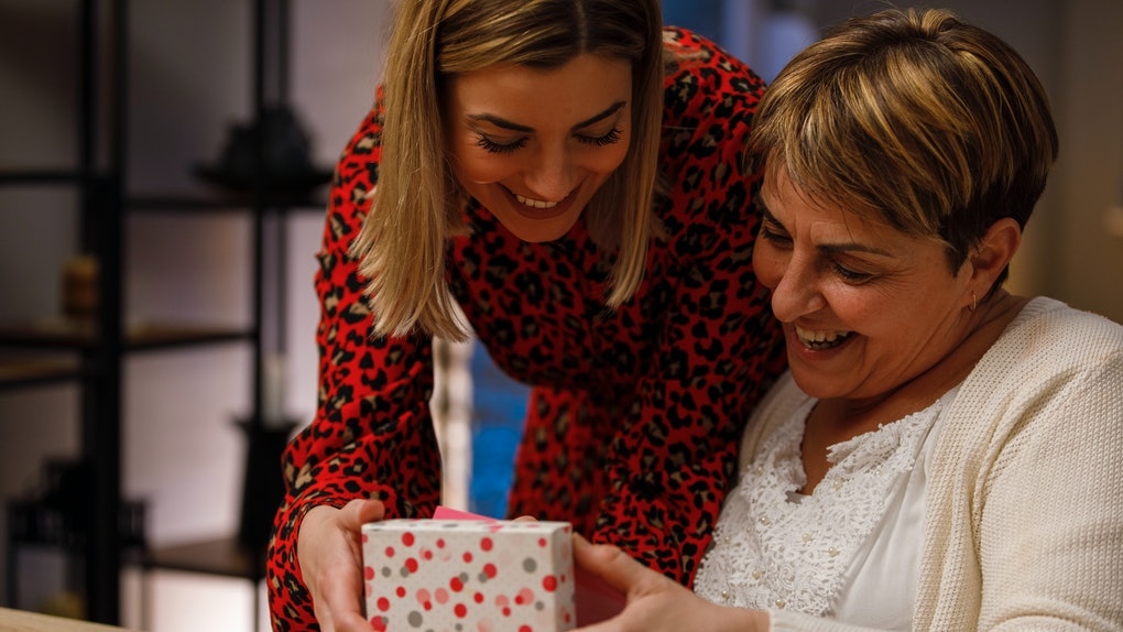 A woman gives her mom a gift box for Mother's Day.