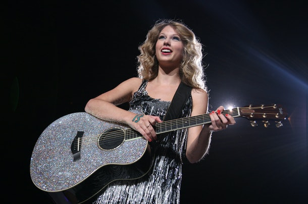 Taylor Swift performing with a silver guitar and dress during her 'Fearless' era.