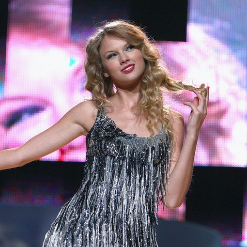 Taylor Swift from her 'Fearless' era stands in a sparkling silver dress onstage.