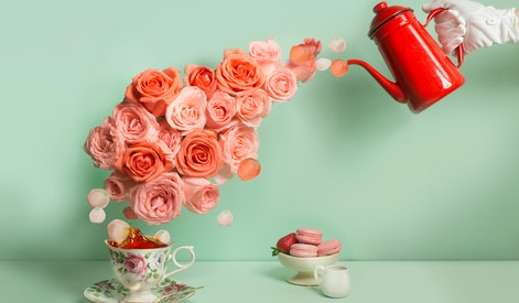 Buttler hand with glove pouring a stream of roses into tea cup on green background. Surreal conceptual afternoon tea image.