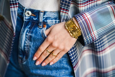 PARIS, FRANCE - FEBRUARY 26: Marine Blanpain wears a golden bracelet, a blue and red checked blazer oversized jacket from Gant, a white t-shirt from Loavies, blue denim jeans pants from Pull & Bear, golden rings, on February 26, 2021 in Paris, France. (Photo by Edward Berthelot/Getty Images)