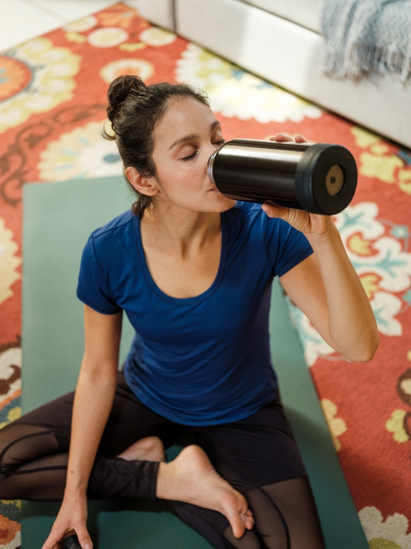 A young latin woman wearing sports clothes at home and drinking water from a reusable bottle after a workout. Staying hydrated after the covid vaccine can help your side effects, doctors say.