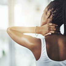 A person faces away from the camera while rubbing one hand on the back of their neck. Even though it's not an official side effect of the COVID vaccine, you might still get muscle cramps after your shot.