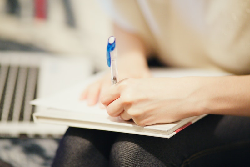 woman writing in her notebook with her left hand