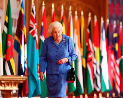 Britain's Queen Elizabeth II walks past Commonwealth flags displayed in St George's Hall at Windsor Castle, Windsor, southeast England on March 5, 2021, to mark Commonwealth Day which is to be celebrated on March 8, 2021. (Photo by Steve Parsons / POOL / AFP) (Photo by STEVE PARSONS/POOL/AFP via Getty Images)