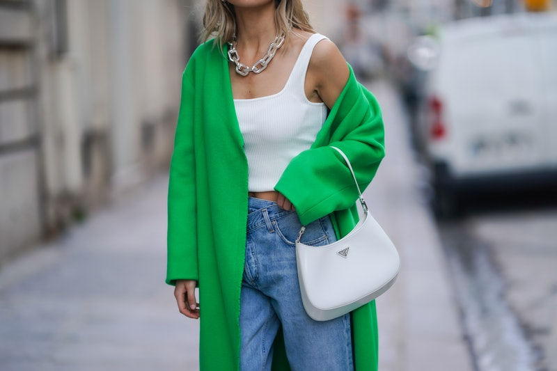 PARIS, FRANCE - MARCH 24: Xenia Adonts wears a chain metallic necklace, a white ribbed knit cropped tank top, a green long wool winter oversize coat from Dorothee Schumacher, blue denim jeans pants from Agolde, a white Prada Cleo bag, on March 24, 2021 in Paris, France. (Photo by Edward Berthelot/Getty Images)