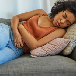 A person wears jeans and a tank top while holding their stomach in pain on a couch. Even though it's not an official side effect, you might get nauseous after getting your COVID vaccine.