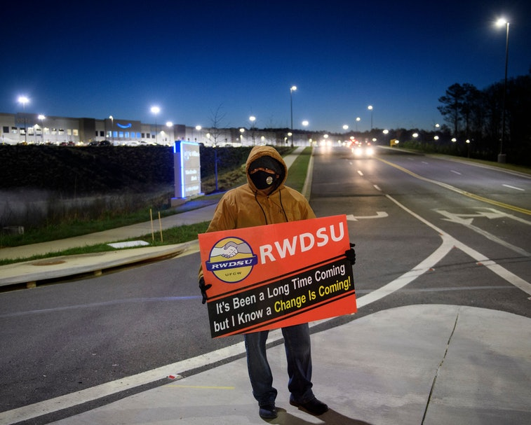 """A union supporter stands before sunrise outside the Amazon.com, Inc. BHM1 fulfillment center on March 29, 2021 in Bessemer, Alabama. - Votes are set to be counted on March 29, 2021 on whether to create the first Amazon union in the United States, at a warehouse in Alabama, after a historic, five months-long David vs Goliath campaign. """"I'm proud of the workers at Amazon for standing up and saying enough,"""" said Joshua Brewer, the local president of the Retail, Wholesale and Department Store Union. (Photo by Patrick T. FALLON / AFP) (Photo by PATRICK T. FALLON/AFP via Getty Images)"""