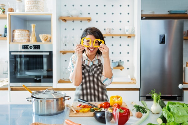 A smiling young woman looks through bell pepper slices in kitchen at home while recreating a TikTok bell pepper sandwich recipe.
