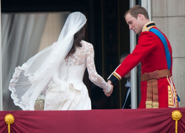 Prince William holds Kate Middleton's hand.