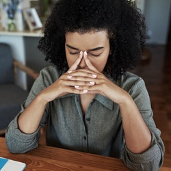 A person puts their index fingers to their temple and closes their eyes while working from home. Anxiety might be the reason you get those sudden chills all the time.