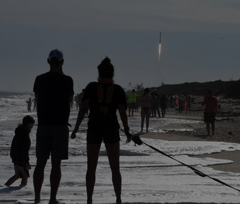 Brandon and Heather Arentson (from left) of Atlanta, Georgia watch from the beach at Canaveral National Seashore as a SpaceX Falcon 9 rocket with the Dragon spacecraft launches from pad 39A at the Kennedy Space Center on December 6, 2020 in Cape Canaveral, Florida. The cargo mission will deliver over 6,400 pounds of crew supplies and research experiments to the International Space Station. (Photo by Paul Hennessy/NurPhoto via Getty Images)