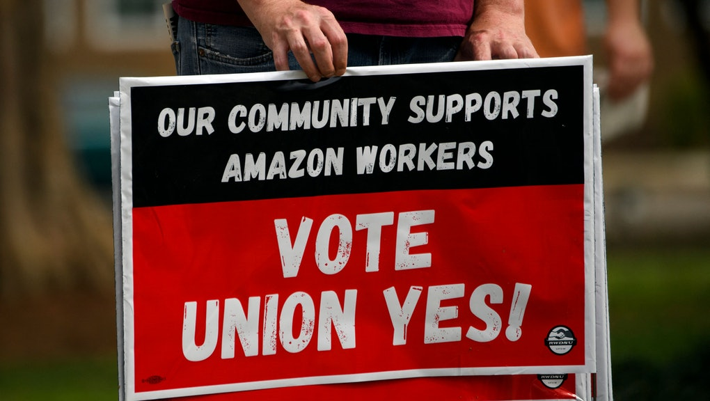 """A person holds """"Vote Union Yes!"""" signs during a protest in solidarity with Black Lives Matter, Stop Asian Hate and the unionization of Amazon.com, Inc. fulfillment center workers at Kelly Ingram Park on March 27, 2021 in Birmingham, Alabama. - Senator Bernie Sanders joined the drive to unionize Amazon workers in Alabama with the Retail, Wholesale and Department Store Union (RWDSU) in Birmingham, as clashes intensified between lawmakers and the e-commerce giant ahead of a deadline for a vote that could lead to the first union on US soil at the massive tech company. The visit marks the latest high-profile appearance in the contentious organizing effort for some 5,800 employees at Amazon's warehouse in Bessemer which culminates next week. (Photo by Patrick T. FALLON / AFP) (Photo by PATRICK T. FALLON/AFP via Getty Images)"""