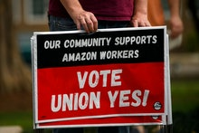 """A person holds """"Vote Union Yes!"""" signs during a protest in solidarity with Black Lives Matter, Stop ..."""