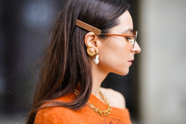PARIS, FRANCE - OCTOBER 01: Julia Comil wears orange clear sunglasses, pearl earrings, a golden necklace, a one shoulder oversized wool orange and blue pullover with flared long sleeves, outside Chloe, during Paris Fashion Week - Womenswear Spring Summer 2021, on October 01, 2020 in Paris, France. (Photo by Edward Berthelot/Getty Images)