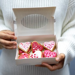 Woman wearing white sweatshirt holding a box with Valentine's cookies in heart forms