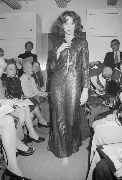 (Original Caption) 11/7/1974: Fashion designer Halston, who's just won every major fashion award around, showed his new collection. In this part of his collection he retains a bit of the traditional with a floor length blue sequined sheath with the neckline cut down to the navel.
