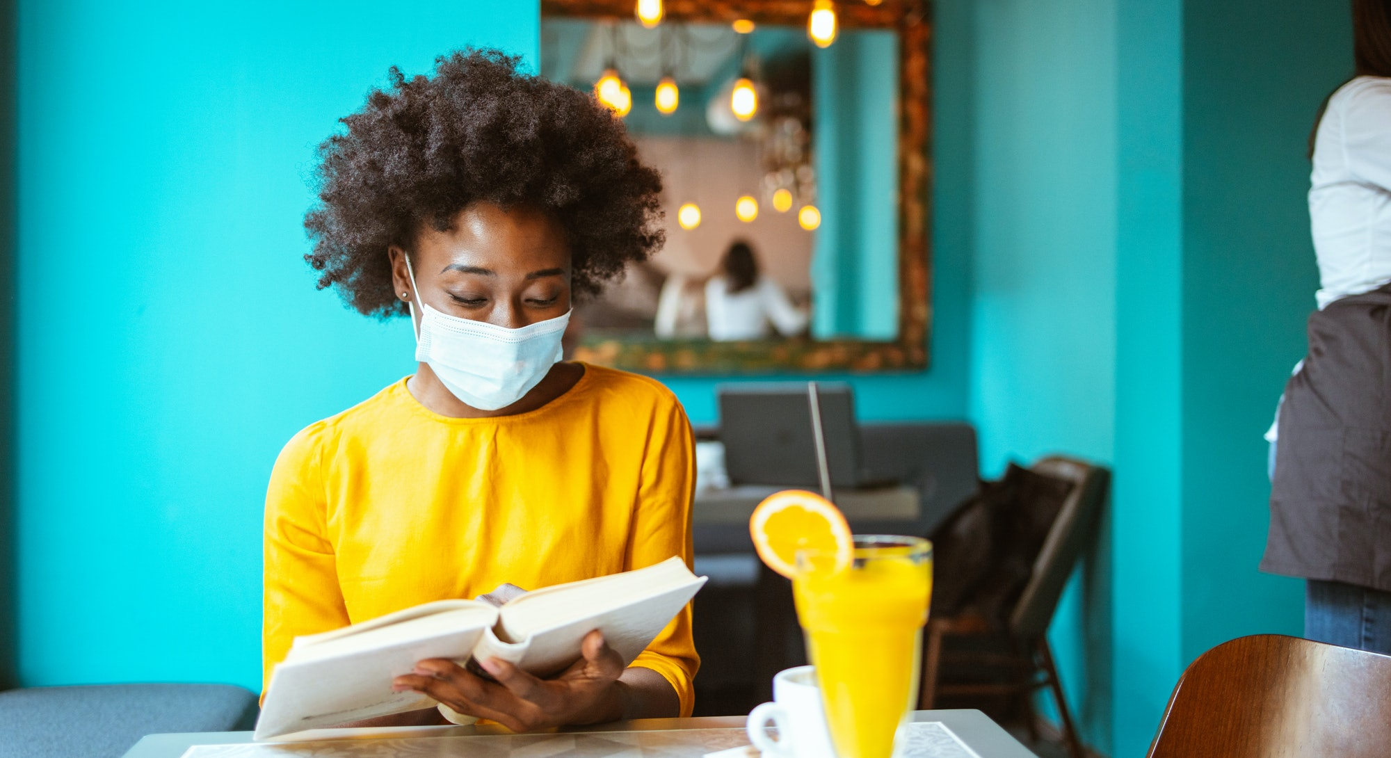 A happy African American woman with protective mask on her face reading book in a coffee shop. New normal.