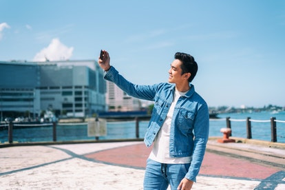 Millennial generation - Handsome Asian man taking selfie in the city
