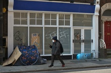A man wearing a face mask walks past a  a rough sleeper's tent outside the entrance to a closed busi...