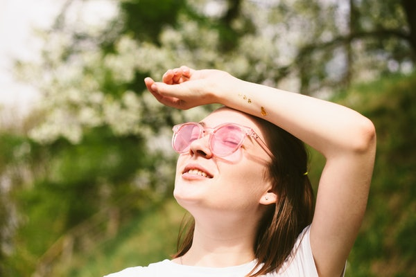 Woman wearing white t-shirt and pink sunglasses relaxing in spring park. Outdoors portrait of young woman walking in forest. Blooming cherry trees.