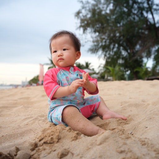 Baby experiencing the beach for the very first time. Mother guiding her baby through her sand and water explorations.