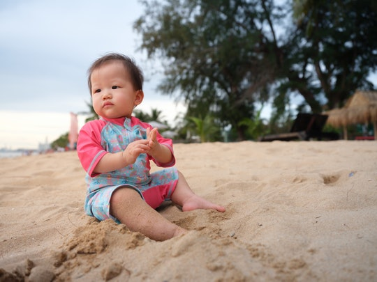Baby experiencing the beach for the very first time. Mother guiding her baby through her sand and wa...